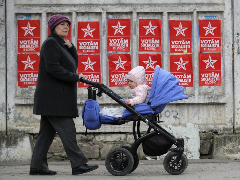 A woman pushes a baby stroller by electoral posters advertising the candidates of the Socialists' Party, in Chisinau, Moldova, Thursday, Feb. (AP Photo/Vadim Ghirda)