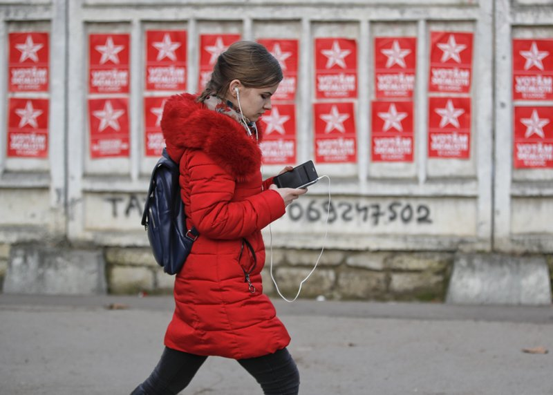 A girl walks by electoral posters advertising the candidates of the Socialists' Party in Chisinau, Moldova, Thursday, Feb. (AP Photo/Vadim Ghirda)