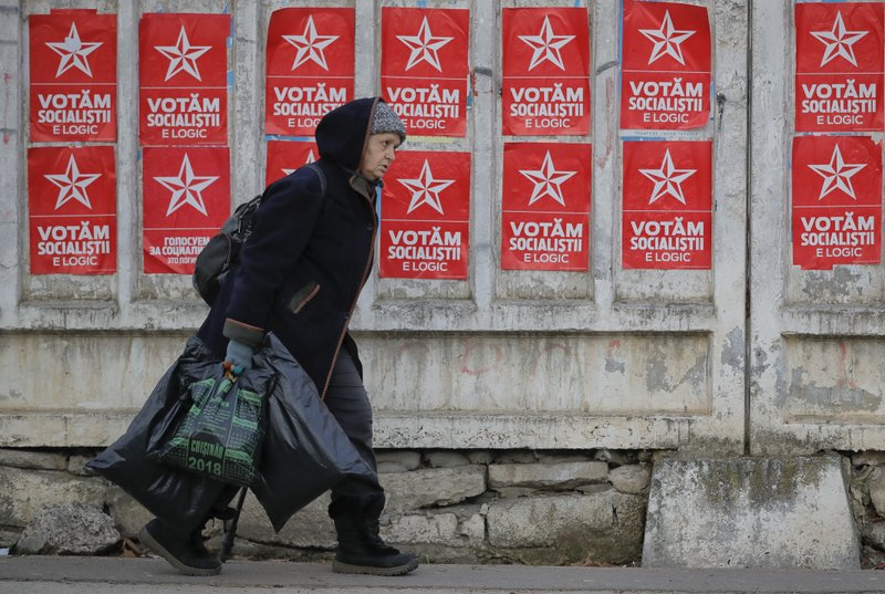 A woman walks by electoral posters advertising the candidates of the Socialists' Party Chisinau, Moldova, Thursday, Feb. (AP Photo/Vadim Ghirda)