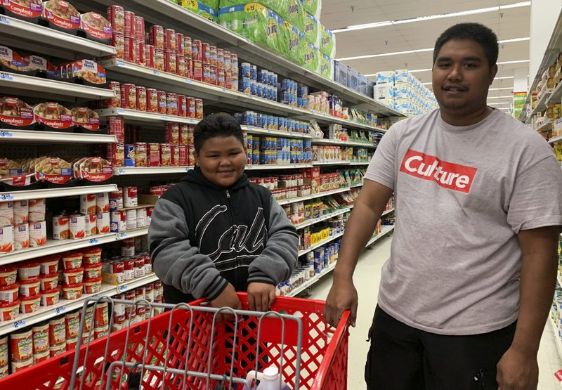 Tyrone Quinata, 23, and his nephew Rayden Gofigan, 11, shop for batteries and other necessities in Tamuning, Guam on Thursday, Feb. (AP Photo/Grace Garces Bordallo)