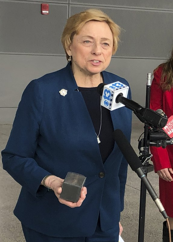 Maine Gov. Janet Mills holds a 1-pound block of carbon to make her point as she talks about her decision to support a transmission project that would bring Canadian hydropower to Massachusetts residents, on Thursday, Feb. (AP Photo/David Sharp)