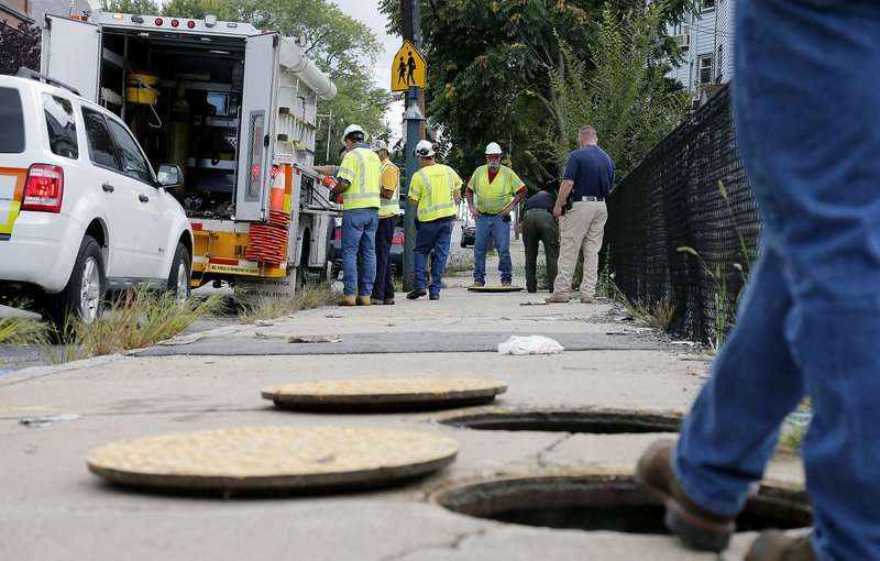 FILE-- In this Sept. 14, 2018 file photo, a worker with Columbia gas stands over an open manhole as the crew works to make sure there are no gas leaks at the corner of Parker and Salem Streets in Lawrence, Mass. (AP Photo/(AP Photo/Mary Schwalm, File)