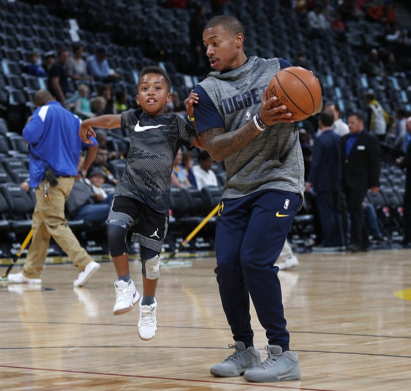 FILE - In this Saturday, Nov. 3, 2018, file photo, Denver Nuggets guard Isaiah Thomas, right, plays with his 6-year-old son, Jaiden, before the first half of an NBA basketball game against the Utah Jazz in Denver. (AP Photo/David Zalubowski, File)