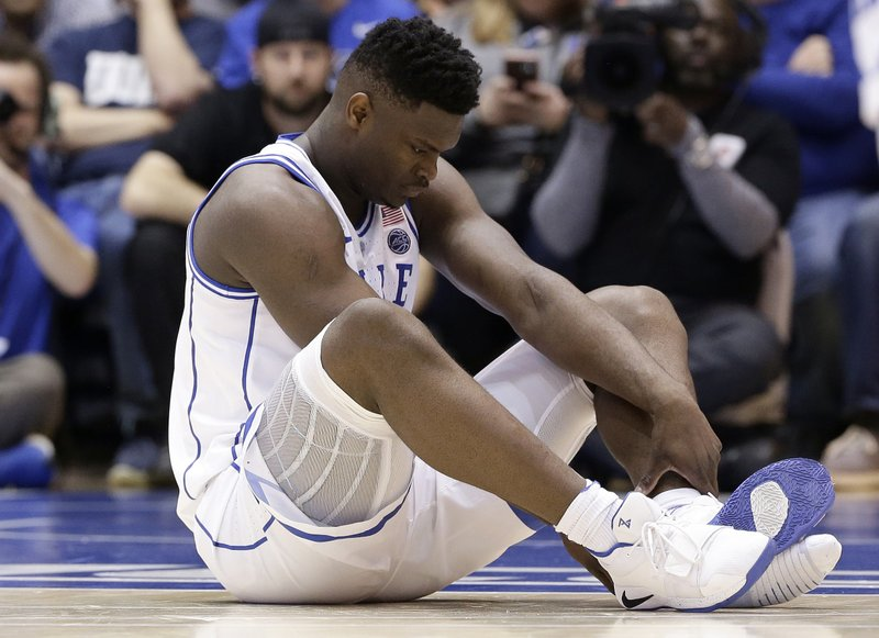 Duke's Zion Williamson sits on the floor following a injury during the first half of an NCAA college basketball game against North Carolina, in Durham, N. (AP Photo/Gerry Broome)