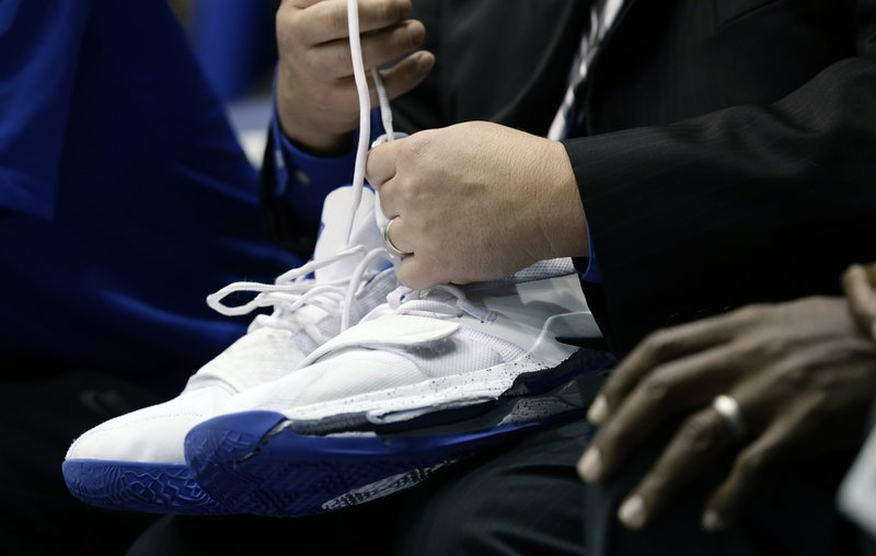 A trainer holds Duke's Zion Williamson's shoes after Williamson left the game due to an injury during the first half of an NCAA college basketball game against North Carolina in Durham, N. (AP Photo/Gerry Broome)