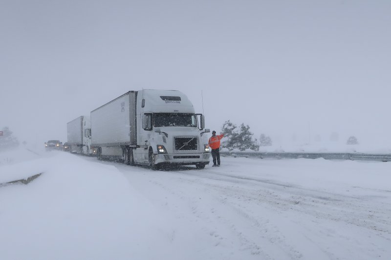 Frank Van Buren, the manager of a travel center, gives direction to semi-truck drivers who are pulling off Interstate 40 in Bellemont, Arizona, on Thursday, Feb. (AP Photo/Felicia Fonseca)