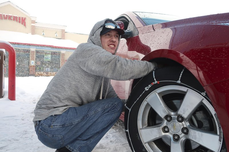 Taylor Killian puts snow chains on the vehicle he's driving during a trip to Flagstaff, Arizona, on Thursday, Feb. (AP Photo/Felicia Fonseca)