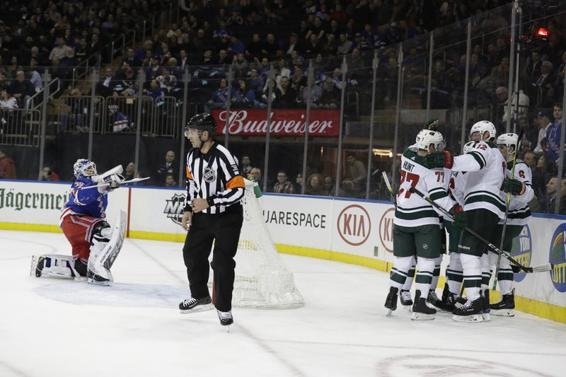 New York Rangers goaltender Henrik Lundqvist, left, gets up as the Minnesota Wild celebrate a goal by Jared Spurgeon during the first period of an NHL hockey game Thursday, Feb. (AP Photo/Frank Franklin II)