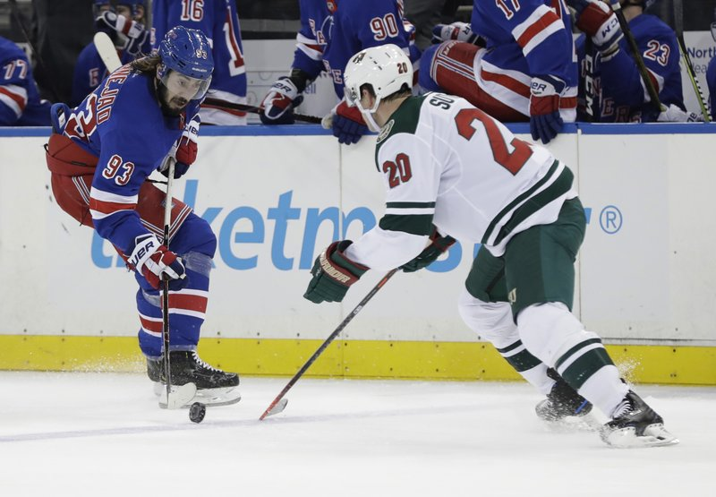 New York Rangers' Mika Zibanejad (93) fights for control of the puck with Minnesota Wild's Ryan Suter (20) during the second period of an NHL hockey game Thursday, Feb. (AP Photo/Frank Franklin II)