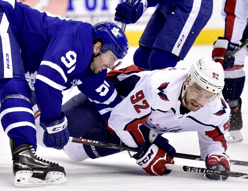 Toronto Maple Leafs center John Tavares (91) and Washington Capitals center Evgeny Kuznetsov (92) vie for control of the puck during first-period NHL hockey game action in Toronto, Thursday, Feb. (Frank Gunn/The Canadian Press via AP)