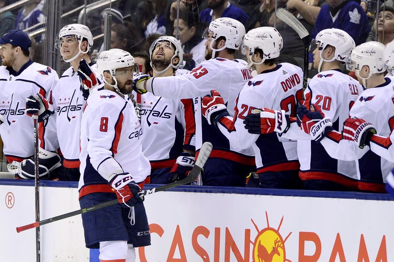 Washington Capitals left wing Alex Ovechkin (8) celebrates his goal with teammates on the bench during second-period NHL hockey game action against the Toronto Maple Leafs in Toronto, Thursday, Feb. (Frank Gunn/The Canadian Press via AP)