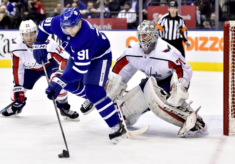Toronto Maple Leafs centreJohn Tavares (91) tries to manage the puck in front of Washington Capitals goaltender Braden Holtby (70) as Capitals' Brooks Orpik (44) looks on during second-period NHL hockey game action in Toronto, Thursday, Feb. (Frank Gunn/The Canadian Press via AP)