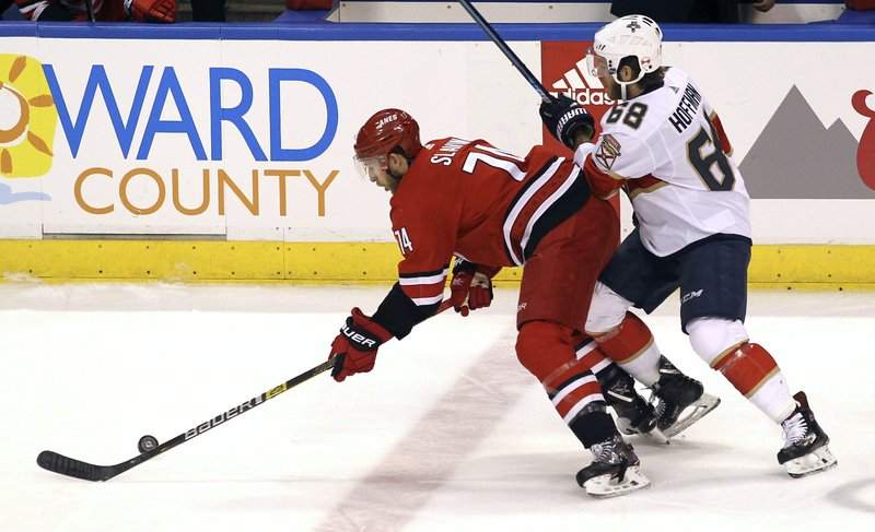 Carolina Hurricanes' Jaccob Slavin, left, and Florida Panthers' Mike Hoffman (68) compete for the puck during the first period of an NHL hockey game Thursday, Feb. (AP Photo/Luis M. Alvarez)