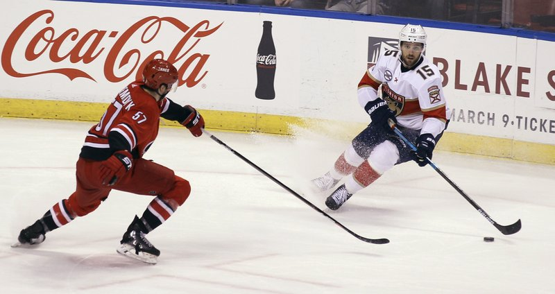 Florida Panthers' Riley Sheahan (15) moves the puck as Carolina Hurricanes' Trevor van Riemsdyk (57) defends during the first period of an NHL hockey game Thursday, Feb. (AP Photo/Luis M. Alvarez)