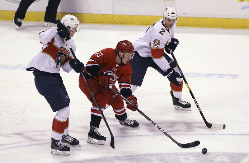 Carolina Hurricanes' Brock McGinn (23) moves the puck as Florida Panthers' Henrik Borgstrom, left, and Josh Brown (2) defend during the first period of an NHL hockey game Thursday, Feb. (AP Photo/Luis M. Alvarez)