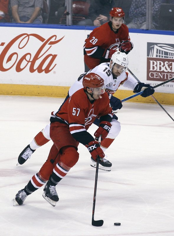 Carolina Hurricanes' Trevor van Riemsdyk (57) takes the puck from Florida Panthers' Riley Sheahan (15) as Carolina Hurricanes' Sebastian Aho (20) watches during the first period of an NHL hockey game Thursday, Feb. (AP Photo/Luis M. Alvarez)