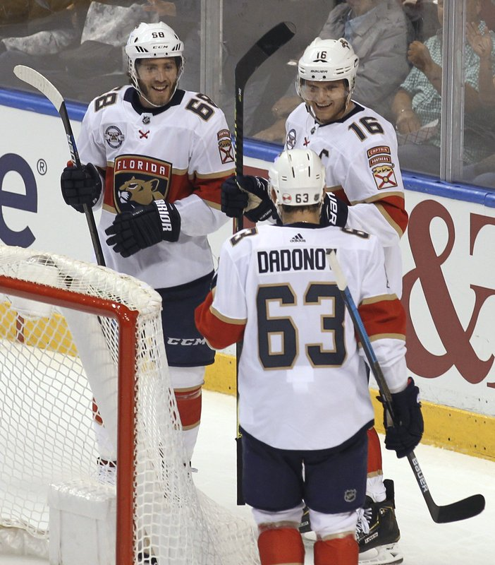 Florida Panthers' Aleksander Barkov (16) celebrates his goal with Mike Hoffman, left, and Evgenii Dadonov (63) during the second period of an NHL hockey game against the Carolina Hurricanes on Thursday, Feb. (AP Photo/Luis M. Alvarez)