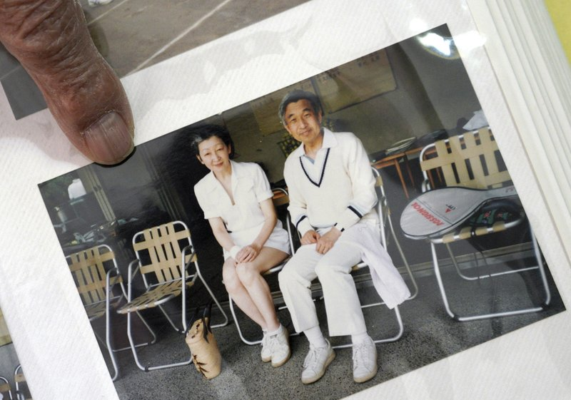 In this Feb. 3, 2019, photo, Kazuo Oda, a retired trading house executive and longtime tennis friend of Emperor Akihito, shows his photo of Akihito and Empress Michiko as they play tennis during an exclusive interview with the Associated Press in Tokyo. (AP Photo/Eugene Hoshiko)