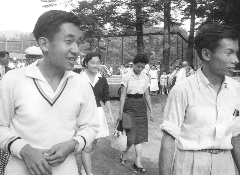 In this August 1958, photo, then Crown Prince Akihito, left, walks with Michiko Shoda, second from left, who married Akihito later, and Akihito's friend Kazuo Oda, right, at a tennis court in Karuizawa, northwest of Tokyo. (Kyodo News via AP)