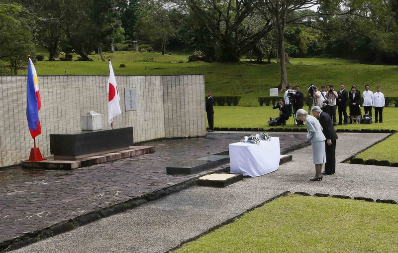 FILE - In this Jan. 29, 2016, file photo, Japan's Emperor Akihito and Empress Michiko bow to pay their respects to the Japanese Imperial Forces who died during WWII at the Japanese Memorial Garden at Cavinti, southeast of Manila, Philippines. (AP Photo/Bullit Marquez, File)