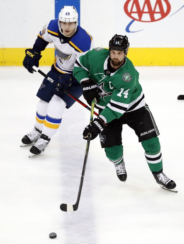 Dallas Stars left wing Jamie Benn (14) controls the puck in front of St. Louis Blues left wing Ivan Barbashev (49) during the first period of an NHL hockey game in Dallas, Thursday, Feb. (AP Photo/Tony Gutierrez)