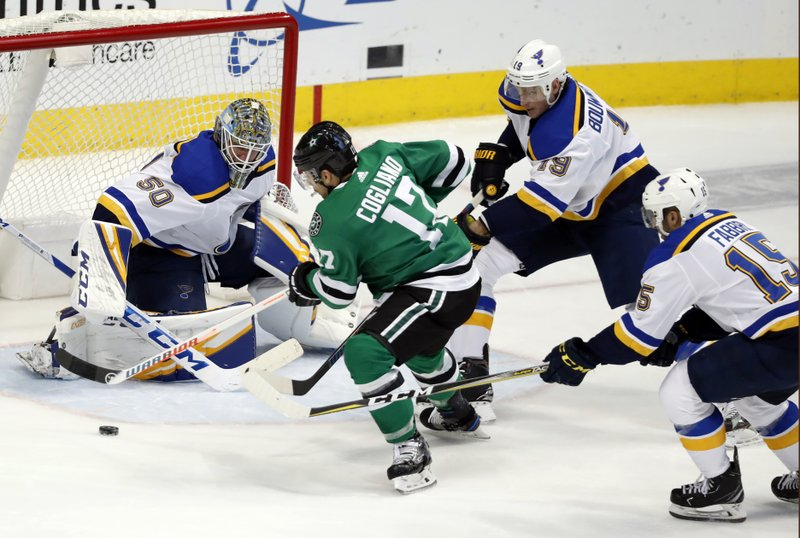 St. Louis Blues goaltender Jordan Binnington (50) gets help from defenseman Jay Bouwmeester (19) and center Robby Fabbri (15) as Dallas Stars center Andrew Cogliano (17) works to take a shot during the first period of an NHL hockey game in Dallas, Thursday, Feb. (AP Photo/Tony Gutierrez)