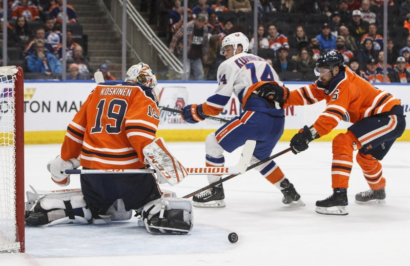 New York Islanders' Tom Kuhnhackl (14) is stopped by Edmonton Oilers goalie Mikko Koskinen (19) as Oilers' Adam Larsson (6) defends during first-period NHL hockey game action in Edmonton, Alberta, Thursday, Feb. (Jason Franson/The Canadian Press via AP)