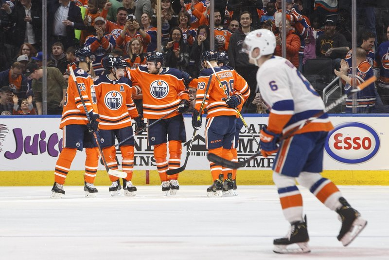 Edmonton Oilers celebrate a goal as New York Islanders' Ryan Pulock (6) skates out of the penalty box during first-period NHL hockey game action in Edmonton, Alberta, Thursday, Feb. (Jason Franson/The Canadian Press via AP)