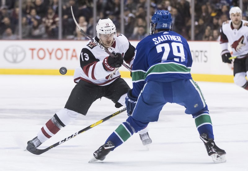 Arizona Coyotes' Vinnie Hinostroza (13) flips the puck past Vancouver Canucks' Ashton Sautner during the first period of an NHL hockey game Thursday, Feb. (Darryl Dyck/The Canadian Press via AP)