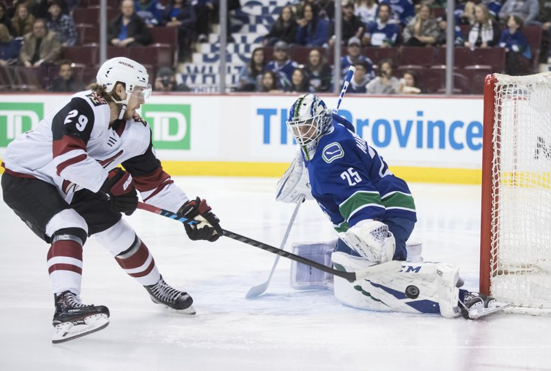 Vancouver Canucks goalie Jacob Markstrom, right, of Sweden, stops Arizona Coyotes' Mario Kempe, of Sweden, during the first period of an NHL hockey game Thursday, Feb. (Darryl Dyck/The Canadian Press via AP)