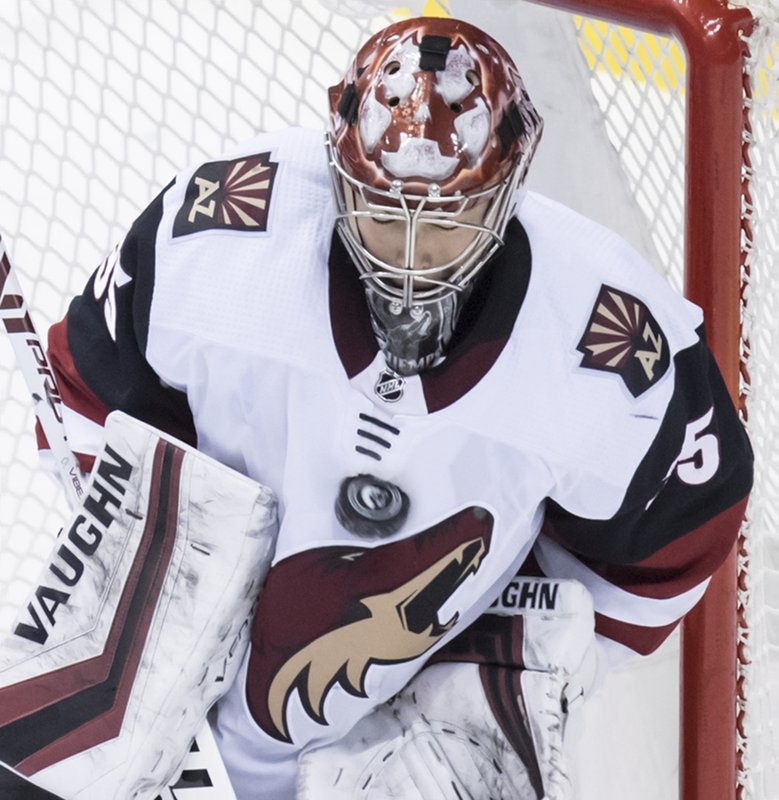 Arizona Coyotes goalie Darcy Kuemper stops a Vancouver Canucks shot during the second period of an NHL hockey game Thursday, Feb. (Darryl Dyck/The Canadian Press via AP)