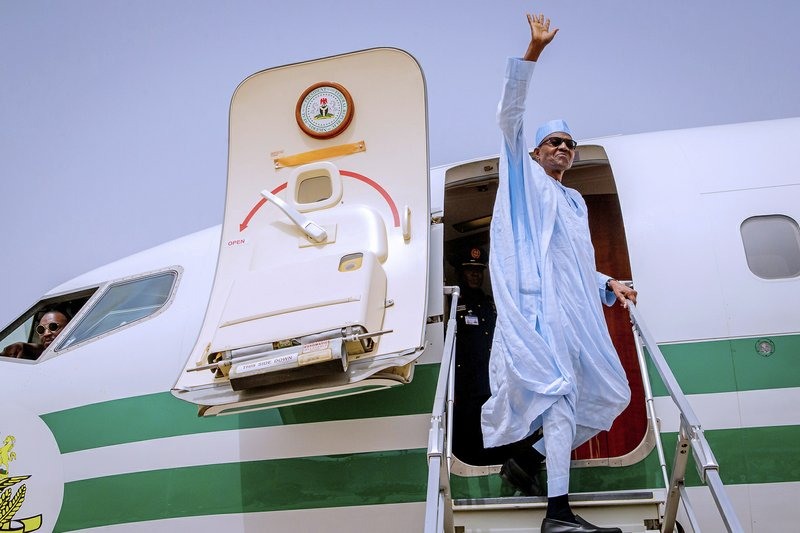 In this photo released by the Nigeria State House, Nigeria Incumbent President Muhammadu Buhari, of the All Progressives Congress party, wave to supporters, as he departs from Daura, Nigeria, to Abuja following the postponement of Nigeria's Presidential election, Saturday, Feb. (Bayo Omoboriowo/Nigeria State House via AP)