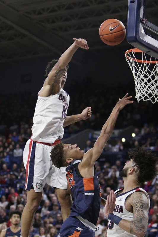 Gonzaga forward Brandon Clarke, top, blocks a shot by Pepperdine forward Kessler Edwards, center, in front of Gonzaga guard Josh Perkins during the second half of an NCAA college basketball game in Spokane, Wash. (AP Photo/Young Kwak)