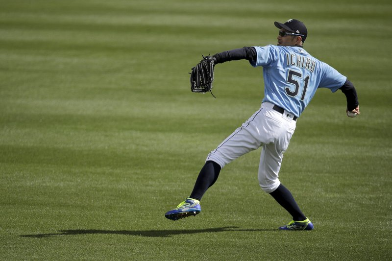Seattle Mariners right fielder Ichiro Suzuki warms up in the outfield before the second inning of a spring training baseball game against the Oakland Athletics, Friday, Feb. (AP Photo/Charlie Riedel)