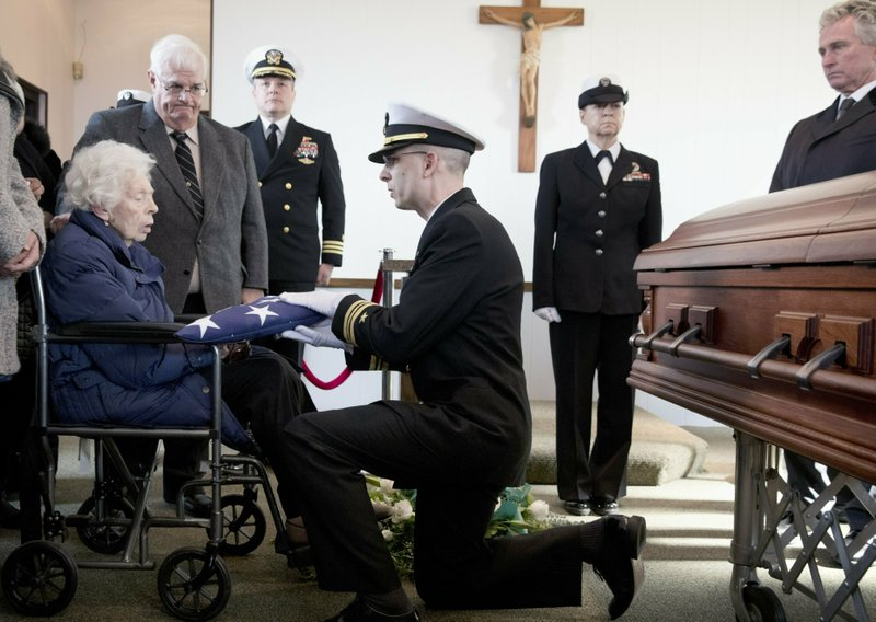 Rita Mendonsa, left, receives the flag that draped her husband George's casket during funeral services at St. (AP Photo/Michael Dwyer)