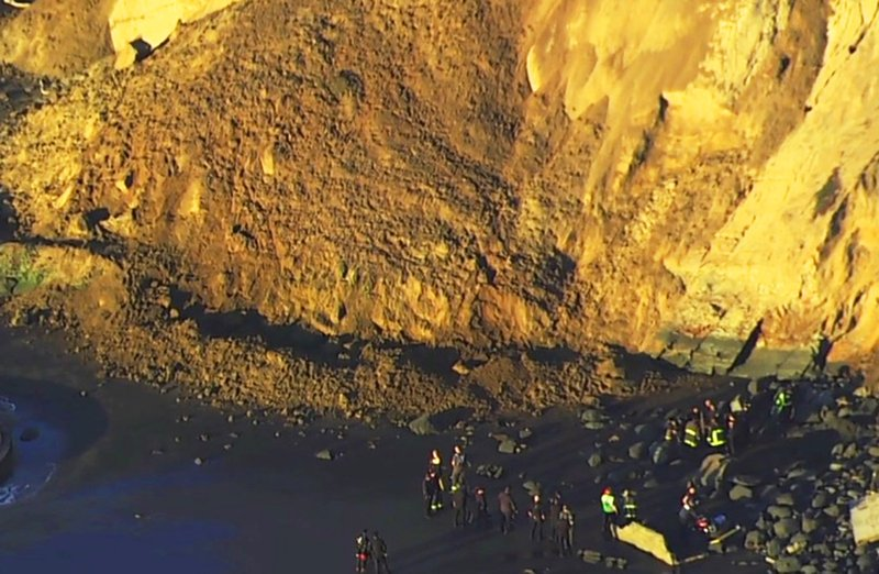 This photo from video provided by KGO-TV shows firefighters searching for a person who was thought to be buried by a landslide near a San Francisco beach Friday, Feb. (KGO-TV via AP)