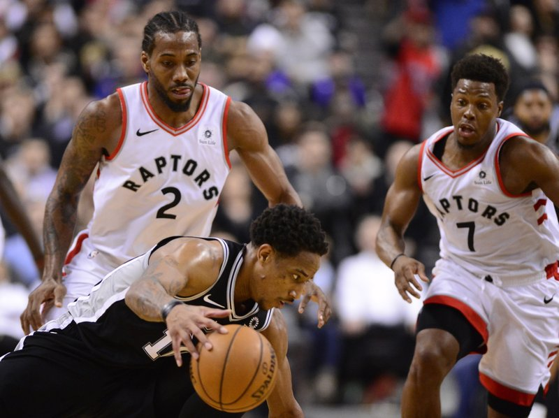 San Antonio Spurs guard DeMar DeRozan (10) loses the the ball under pressure from Toronto Raptors forward Kawhi Leonard (2) with about 15 seconds left in an NBA basketball game Friday, Feb. (Frank Gunn/The Canadian Press via AP)
