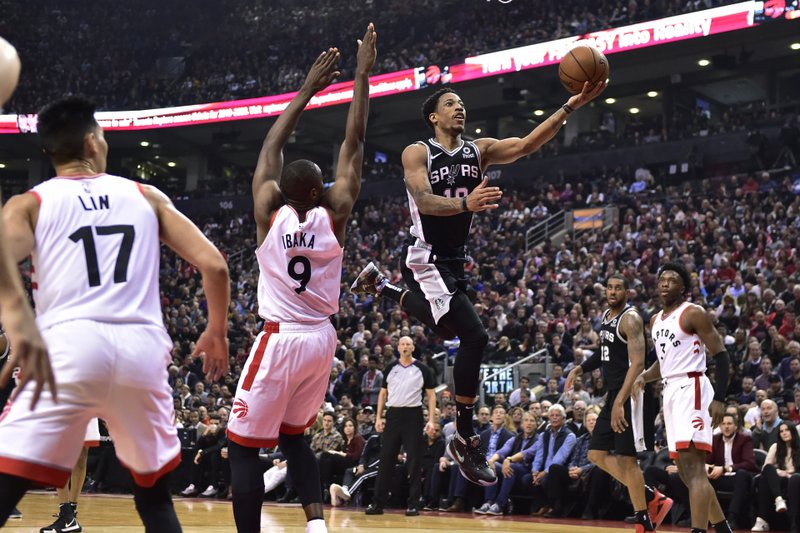 San Antonio Spurs guard DeMar DeRozan (10) leaves the Raptors standing as he makes a 360 move to score during the first half of an NBA basketball game Friday, Feb. (Frank Gunn/The Canadian Press via AP)