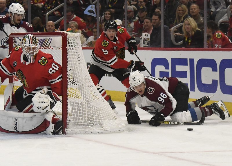 Colorado Avalanche right wing Mikko Rantanen (96) goes for the puck as Chicago Blackhawks goaltender Collin Delia (60) defends the net during the first period of an NHL hockey game Friday, Feb. (AP Photo/David Banks)