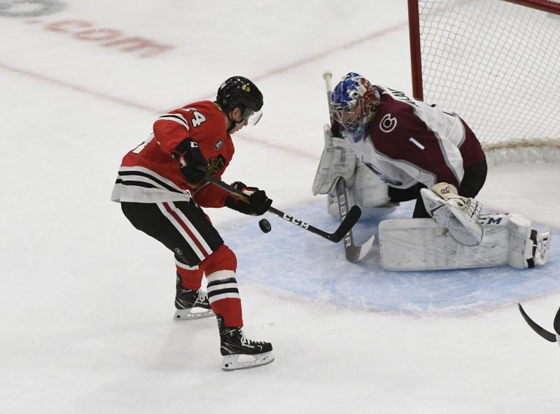 Chicago Blackhawks center Dominik Kahun (24) shoots on Colorado Avalanche goaltender Semyon Varlamov (1) during the second period of an NHL hockey game Friday, Feb. (AP Photo/David Banks)