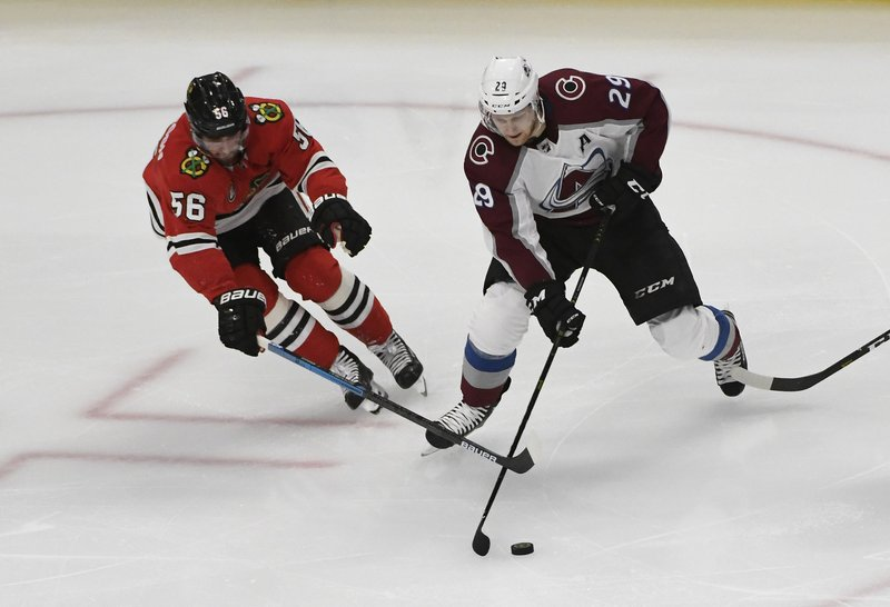 Colorado Avalanche center Nathan McKinnon (29) is defended by Chicago Blackhawks defenseman Erik Gustafsson (56) during the second period of an NHL hockey game Friday, Feb. (AP Photo/David Banks)