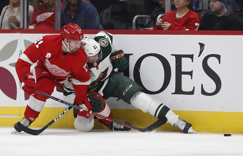 Detroit Red Wings center Dylan Larkin (71) checks Minnesota Wild center Eric Fehr (21) into the boards during the first period of an NHL hockey game Friday, Feb. (AP Photo/Carlos Osorio)