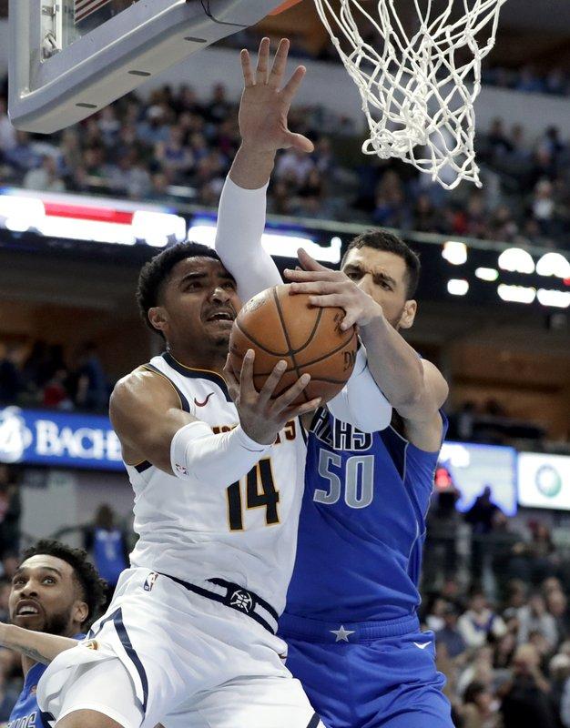 Denver Nuggets guard Gary Harris (14) has his shot attempt blocked by Dallas Mavericks' Salah Mejri (50) during the first half of an NBA basketball game in Dallas, Friday, Feb. (AP Photo/Tony Gutierrez)