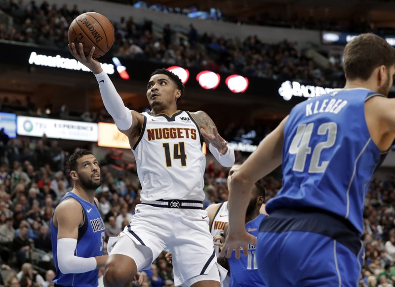Denver Nuggets guard Gary Harris (14) goes up for a shot after getting past Dallas Mavericks' Salah Mejri, left, and Maximilian Kleber (42) during the first half of an NBA basketball game in Dallas, Friday, Feb. (AP Photo/Tony Gutierrez)