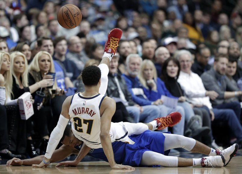Dallas Mavericks guard Devin Harris (34) trips Denver Nuggets guard Jamal Murray (27) during the first half of an NBA basketball game in Dallas, Friday, Feb. (AP Photo/Tony Gutierrez)