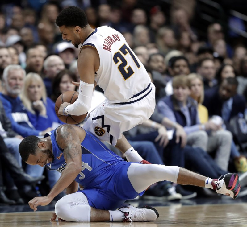Dallas Mavericks guard Devin Harris (34) trips Denver Nuggets guard Jamal Murray (27) as the two chased a loose ball during the first half of an NBA basketball game in Dallas, Friday, Feb. (AP Photo/Tony Gutierrez)