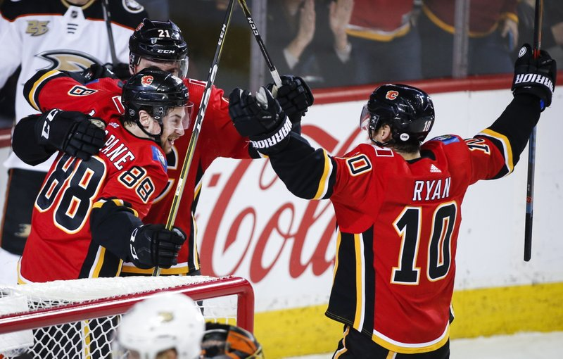 Calgary Flames' Andrew Mangiapane, left, celebrates his goal with teammates during the third period of an NHL hockey game against the Anaheim Ducks on Friday, Feb. (Jeff McIntosh/The Canadian Press via AP)