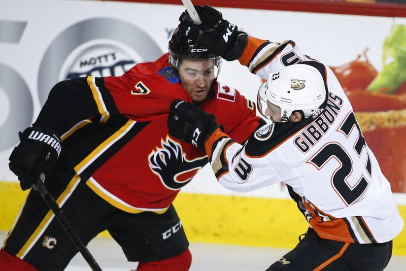 Anaheim Ducks' Brian Gibbons, right, tries to get past Calgary Flames' T.J. Brodie during the second period of an NHL hockey game Friday, Feb. (Jeff McIntosh/The Canadian Press via AP)