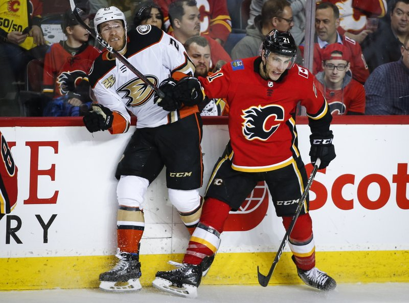 Anaheim Ducks' Carter Rowney, left, is checked by Calgary Flames' Garnet Hathaway during the second period of an NHL hockey game Friday, Feb. (Jeff McIntosh/The Canadian Press via AP)