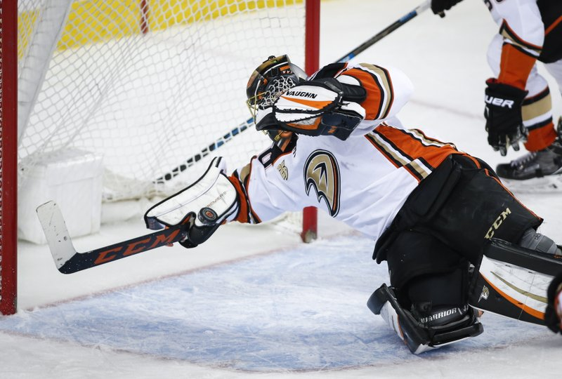 Anaheim Ducks goalie Ryan Miller makes a diving save against the Calgary Flames during the first period of an NHL hockey game Friday, Feb. (Jeff McIntosh/The Canadian Press via AP)